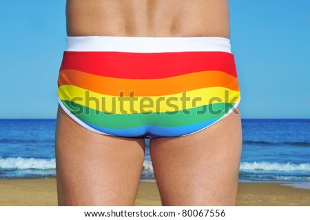 someone wearing a rainbow swimsuit on the beach - stock photo