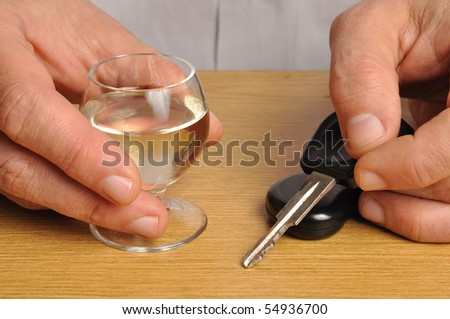 Someone with alcohol and car keys on a table - stock photo