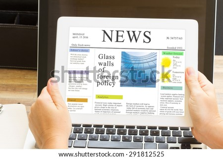 someones hands holding tablet with news site - stock photo