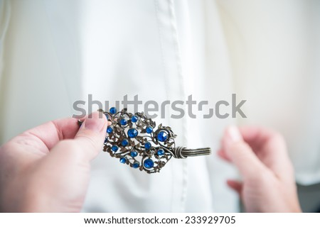 Something old, something new, something borrowed, something blue: Maid of honor pins antique brooch with blue gems on on bride's dress - stock photo