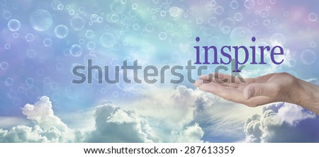 Something to Inspire You - Man's open hand with the word inspire floating above against a wide multicolored sky background, and various cloud formations and different sized bubbles floating across - stock photo