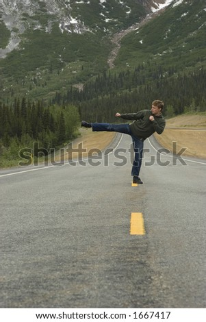Sometimes people want to show what they can do right on the road. Kata in the middle of Alaska. - stock photo