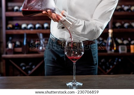 Sommelier pouring wine to the glass in the wine cellar - stock photo