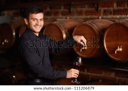 Sommelier pours wine from a barrel - stock photo