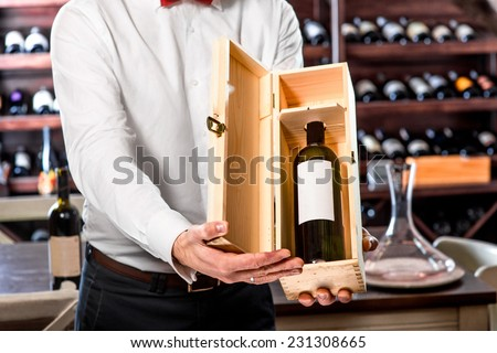 Sommelier showing wooden wine box with expensive wine in the wine cellar - stock photo