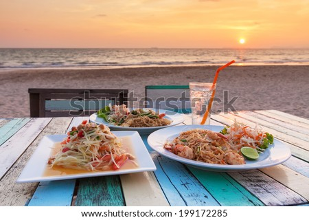 Somtum ,Pad Thai, Stir fry noodles with shrimp - and the view of  sunset at Banana Garden Home on Klong Dao Beach - Lanta Island - Krabi - Thailand. - stock photo