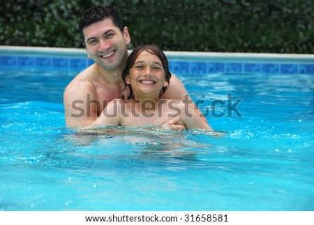 Son and dad enjoying the swimming pool. - stock photo