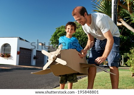 son and dad playing with toy airplane in the garden at home having fun together and smiling - stock photo