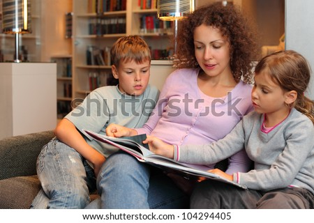 Son and daughter with their mother sit on sofa and read book in room; focus on woman - stock photo