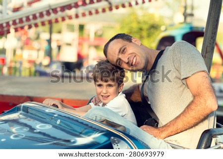 Son and father in the amusement park. - stock photo