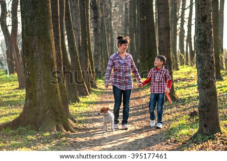 Son and mom with dog in park - stock photo