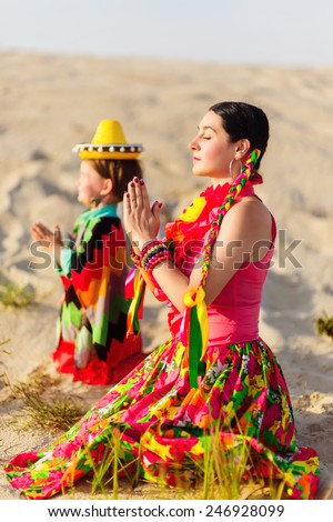 son and mother dressed in Mexican clothes praying together - stock photo