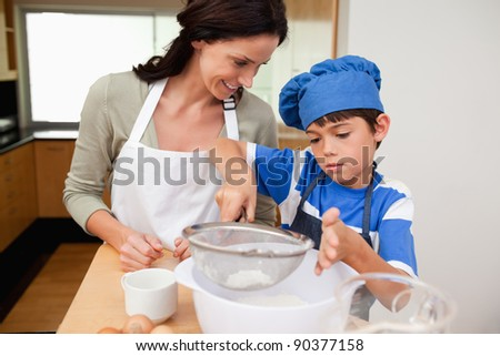 Son and mother preparing dough together