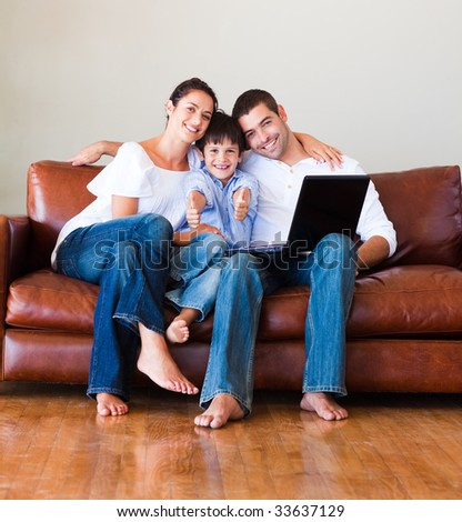 Son and parents playing with a laptop and smiling at the camera - stock photo