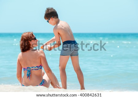 Son applying sunblock cream on his mother shoulder during summer vacation - stock photo
