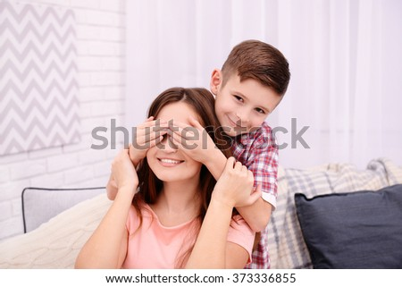 Son closing his mother eyes with his hands - stock photo
