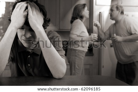 Son cries as parents fight - moody chiaroscuro version - stock photo