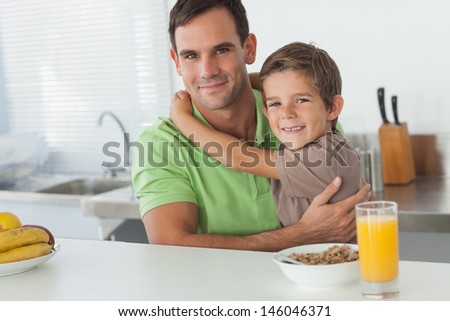 Son embracing his father while having breakfast in the kitchen - stock photo