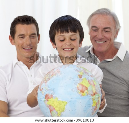 Son, father and grandfather looking at a terrestrial globe at home - stock photo