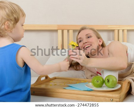 Son gives mom a flower. Mother lying on the bed , next to a table for breakfast - stock photo
