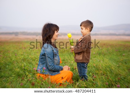 Son gives tulip to his mother. Woman and child lie on the autumn meadow.
