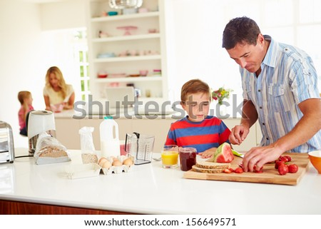 Son Helping Father To Prepare Family Breakfast In Kitchen - stock photo