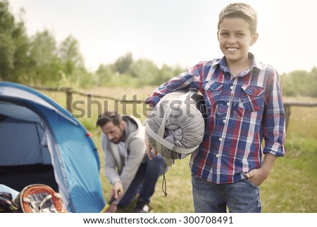 Son helping his father on camping - stock photo