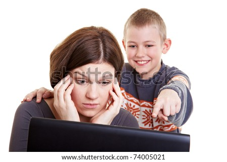 Son helping his mother with her computer problems - stock photo