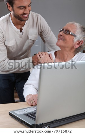 Son helping mother on laptop - stock photo