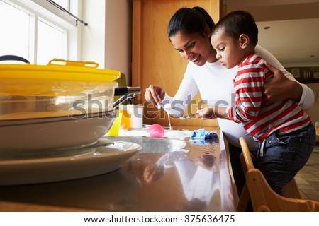 Son Helping Mother To Wash Dishes In Kitchen Sink - stock photo
