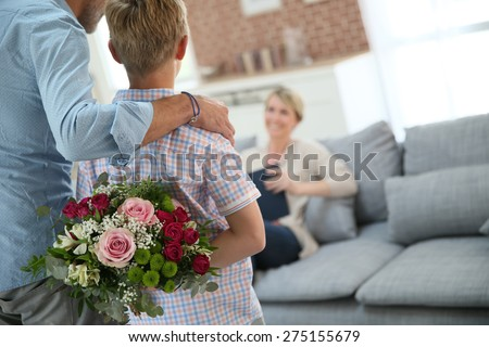 Son hiding bouquet to surprise mommy on mother's day - stock photo