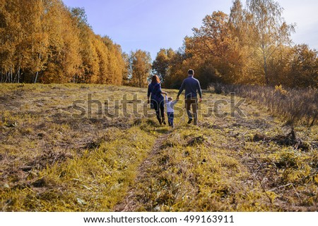 Son holding hands his father in sunny autumn day.