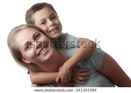 Son hugging his mother from behind and she smiling isolated on white background