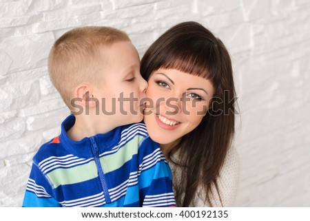 Son kisses mother, mother smiling, close-up shot - stock photo