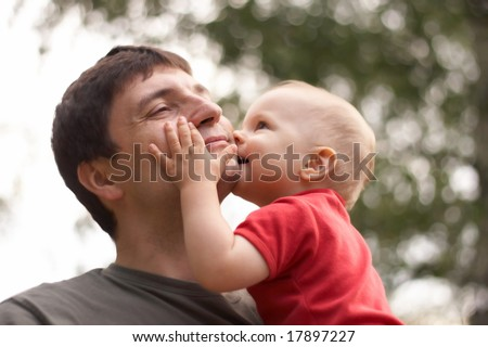 son kissing his father, focus on the hand - stock photo