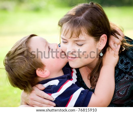 Son kissing mother while playing outside on Mother's Day. - stock photo
