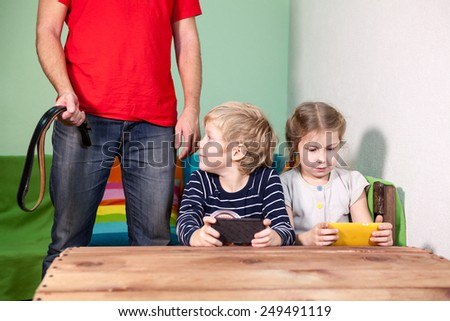 Son looking at belt in the hands of his father while playing phone with sister - stock photo