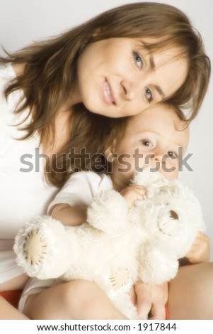 Son nibbling his cuddlebear in mother arms