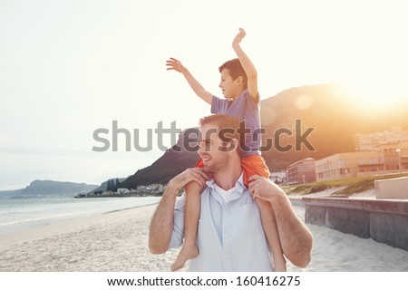 Son on fathers shoulders at the beach having fun at sunset together - stock photo