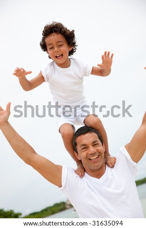 son on his father's shoulders having fun - stock photo