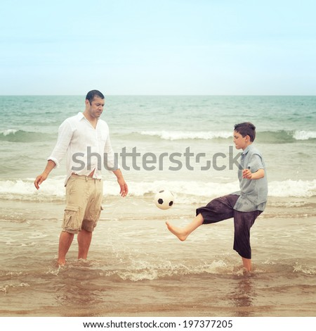 Son playing with a football on the beach while his father watches - stock photo