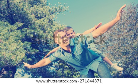 Son playing with his dad outside in a park on a summers day - stock photo