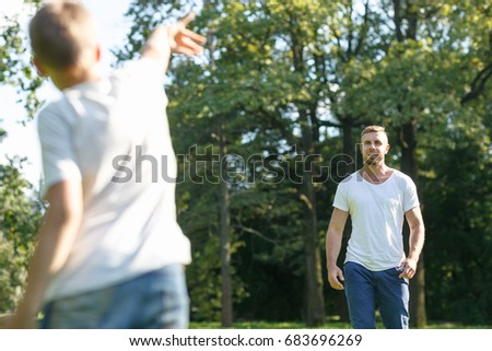 Son playing with his father in a rugby ball throwing it to each other in the summer park. Young cute man and boy dressed in white t-shirts and jeans playing with a ball outside the city.