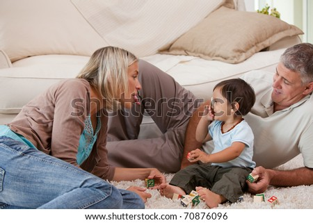 Son playing with his parents at home - stock photo