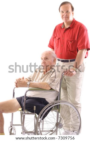 son pushing father in wheelchair - stock photo