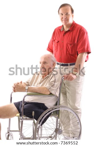 son pushing his father in a wheelchair - stock photo