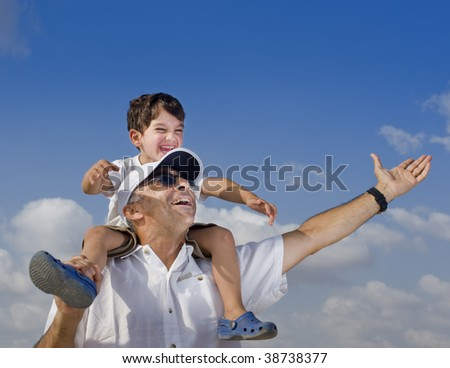 son riding on his father shoulders with spread arms - stock photo