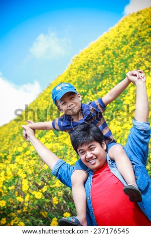 Son sat on father Asians shoulders. - stock photo