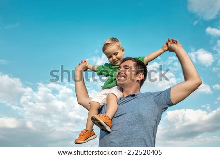 Son seating on the father under beautiful sky with sun - stock photo