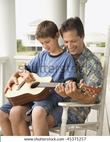 Son sits on his father's lap while playing guitar. Vertical shot. - stock photo